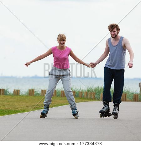 Active holidays exercises relationship concept. Young woman and man dressed up in sporty way holding their hands while inline skating together on promenade.