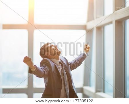 Successful businessman raise his hands up celebrates victory on a sunny day