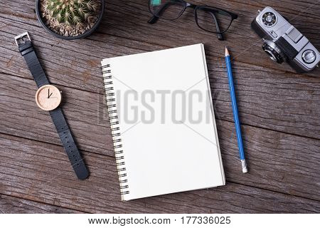 Top view of Notebook Camera cactus wristwatch and pencil on wood background.