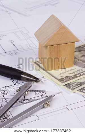 House shape made of wooden blocks accessories for drawing and currencies dollar on electrical construction drawings concept of building house drawing for projects