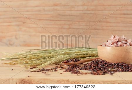 The Brown Rice In Bowl With Ear Of Pappy Rice On Wooden Table