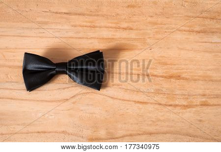 the black bow tie on wooden background