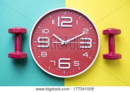 Time for exercising clock and dumbbell with colorful background
