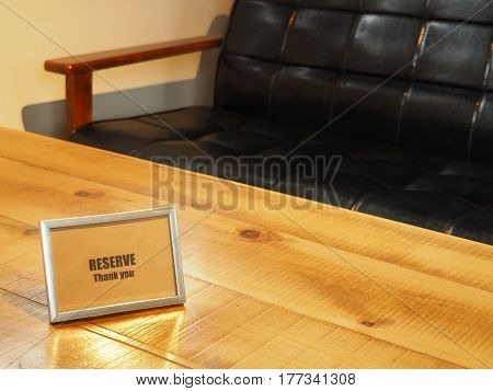Reserved sign on wooden table with black sofa in restaurant.