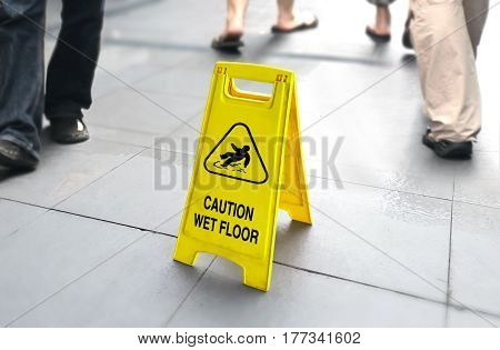 Wet floor sign with people walking in background