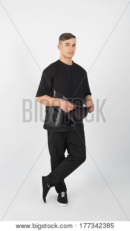 Young muscular man wearing black clothes and sneakers holding snapback isolated on white background