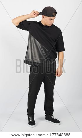 Young muscular man wearing black clothes and sneakers isolated on white background. He is holding snapback and looking down.