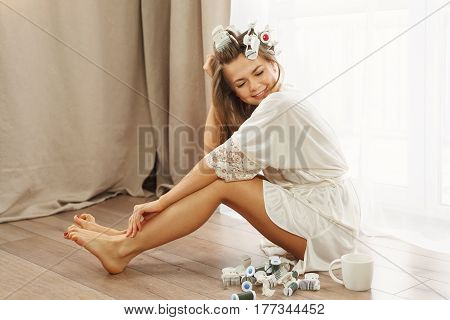 Young attractive housewife sitting on the floor near the window. Girl in a bathrobe and curlers drinking morning coffee. Good morning. She removes hair curlers