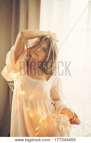Young lovely housewife with a garland. Girl in sexy gown. Good morning. Curvy figure. Soft focus. Toning.