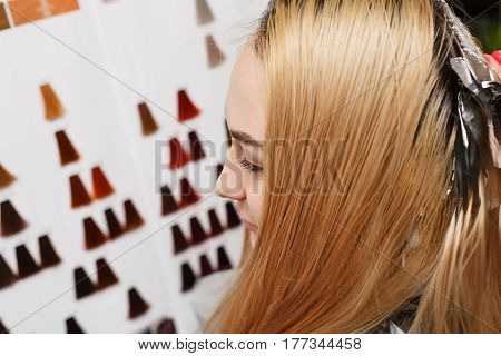 Professional hairdresser holds client's hair coloring. The client chooses a hint of hair dye. Beauty saloon.