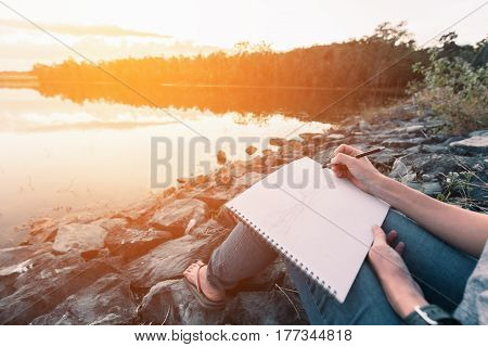 Body of girl sitting on rocks and pencil drawing a view of forest surround pool. Orange bright light on afternoon sky before sunset.