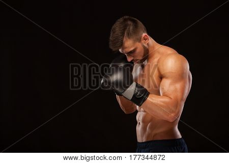 Muscular young man with perfect Torso with six pack abs, in boxing gloves is showing the different movements and strikes isolated on black background with copyspace.