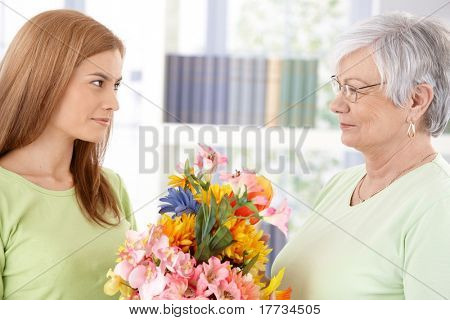 Attractive young woman greeting her mother at mother's day, giving flowers.?