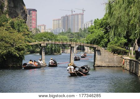 August 27 2016. Shaoxing China. Chinese oarsmen sitting in the wu peng chuan or the black canopied boats on the canals of east lake (dong Hu) in the city of Shaoxing China in Zhejiang province.