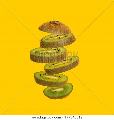 Flying kiwi. Sliced kiwi isolated on yellow background. Levity fruit floating in the air.