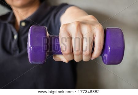 Woman Hand Holding Violet Dumbbell stock photo