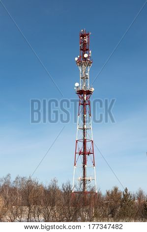 Cellular tower with antenna on the background of a clear blue sky