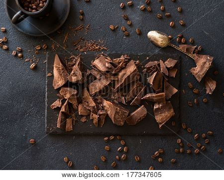 Pieces of bittersweet dark chocolate spread out on a dark background
