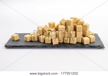 Pile of cane sucar cubes and one cube alone on rectangular dark shale plate on white background