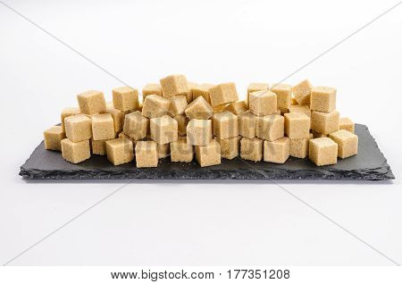 Pile of cane sucar cubes on rectangular dark shale plate on white background