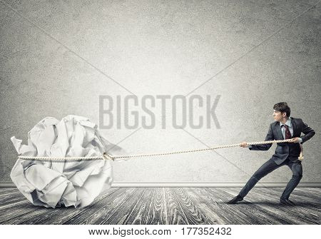 Young man making huge paper ball move