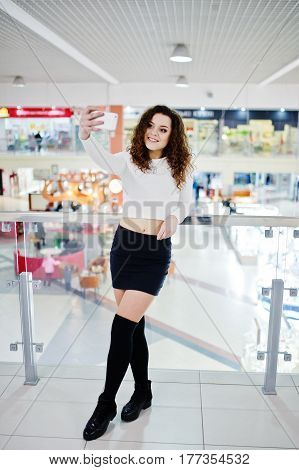 Young Curly Model Girl Making Selfie At Large Shopping Center Near Glass Railings.