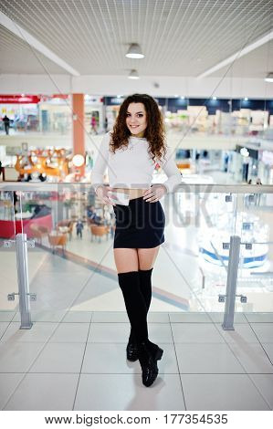 Young Curly Model Girl With Phone At Hand Posed On Mini Skirt At Large Shopping Center Near Glass Ra