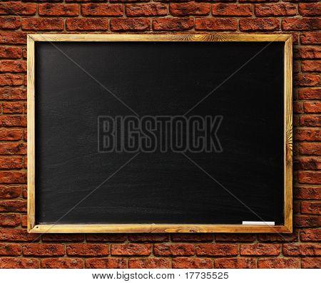 Blank chalkboard in wooden frame on brick wall