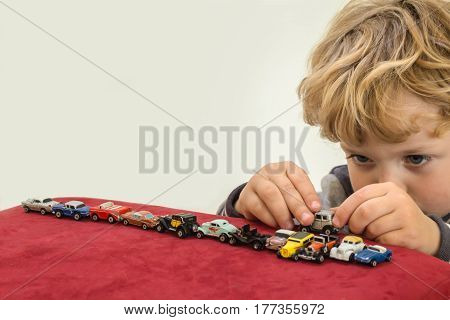 QUEENSTOWN SOUTH AFRICA - MAY 17 2015 - Little blonde boy playing with vintage toy cars on red velvet pouf chair - Editorial Illustrative Image