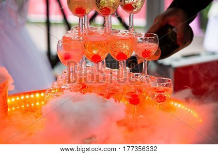 Orange lit a pyramid of champagne glasses. Pouring wine into wineglasses. Festive luxury alcohol at the Banquet.