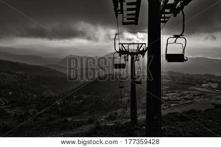 Ski-lift silhouette against beautiful sundown background. Winter season in high mountains.