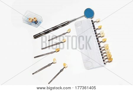 Dental color guide and mirror small box with dentures on a white background