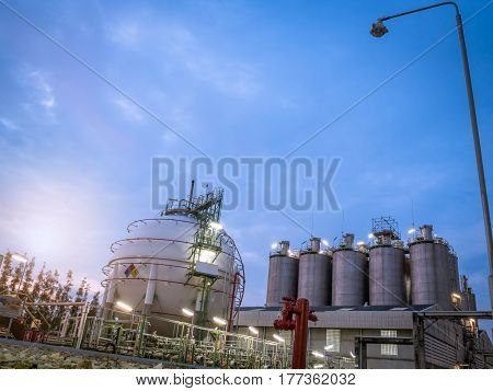 sphere storage gas tank with silos background at dawn