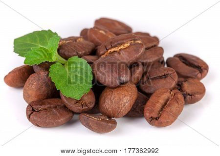 Pile of coffee beans with a mint leaf isolated on white background.