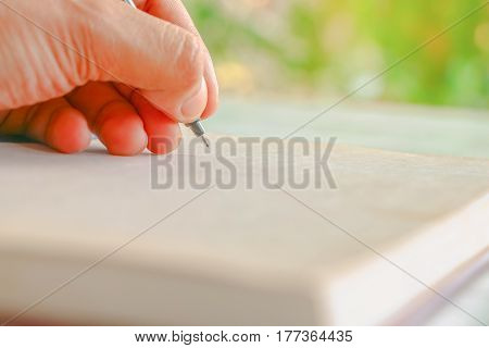 Human hand showing white something on paper at nature with sunlight and bokeh background