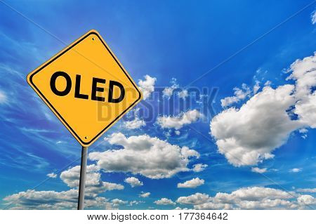 Background of blue sky with cumulus clouds and yellow road sign with text OLED