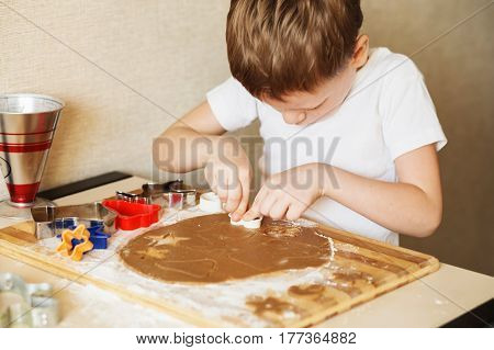 Children's Hands Make Gingerbread. Small Boy Cutting Cookies For Christmas. Kid Baking Cooking Cooki