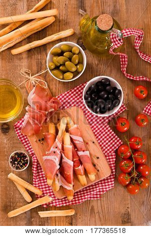 Grissini breadsticks with ham and olives on wooden table.