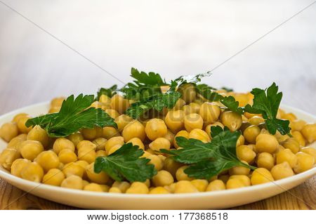 Parsley and chickpeas. Plate of cooked cheak peas and leaves of fresh parsley on a plate on wooden table background
