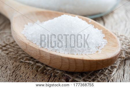 Spoon with white sugar on the wooden background