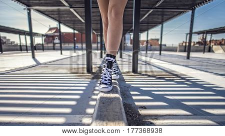 Details Of Woman Legs Walking On Concrete Ledge In Her Classic Sneakers