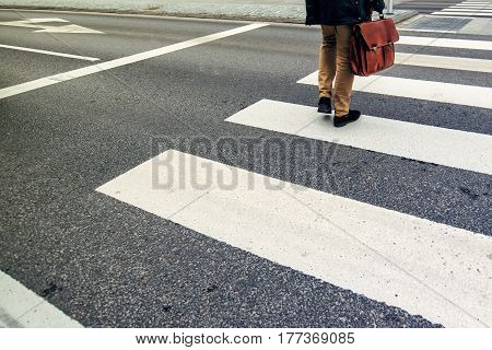 Unrecognizable businessman walking over pedestrian zebra crossing on his way to work