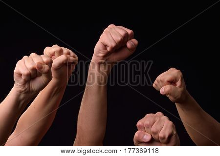 Group of female and male hands showing fists raised up on black background. Team. Power. Leader. Revolt