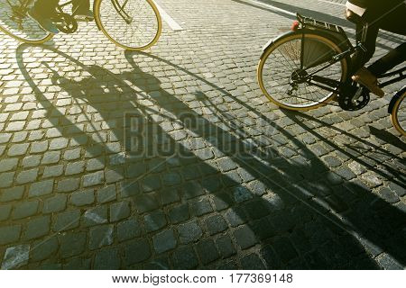 City cyclists people riding bicycles on cobblestone road shadow of person on the bike