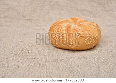 Freshly Baked Whole Grain Round Sandwich Bun Sprinkled With Sesame Seeds On Jute Background. Whole G