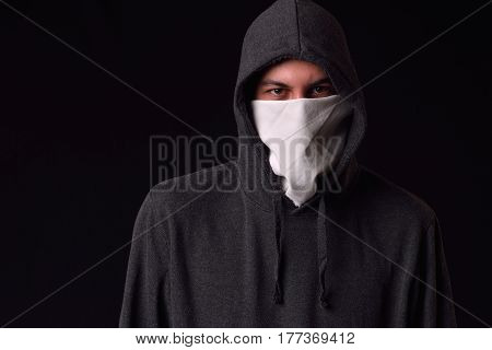 Unrecognizable young man wearing white balaclava and black hoodie ready to protest at a rally on a dark background