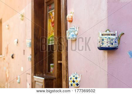Vilnius Lithuania - August 8 2012: Vintage ceramic teapots embedded in facade corner of historic building on main street of old town. Inscription on kettle indicates address Bernardine street