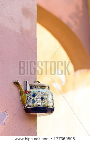 Vilnius Lithuania - August 8 2012: Vintage ceramic teapot embedded in facade corner of historic building on main street of old town. Inscription on kettle indicates address Bernardine street