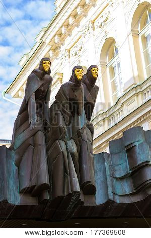 Vilnius Lithuania - August 8 2012: Three graces on roof of entrance to national drama theatre of Lithuania. Women-nuns in black robes with Golden masks on face. Creative sculptures out of copper