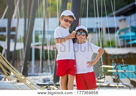Two Beautiful Children, Boy Brothers, Standing On A Boat, Smiling